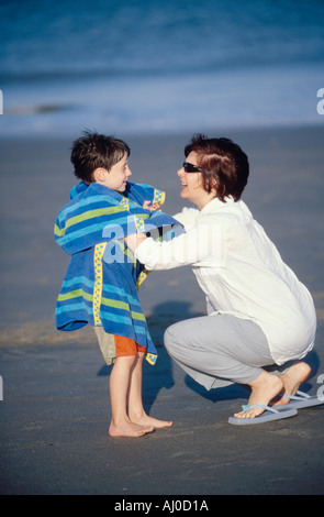 A smiling young boy receives a vigorous toweling down on the beach by his happy mother after he emerges from the - Stock Photo