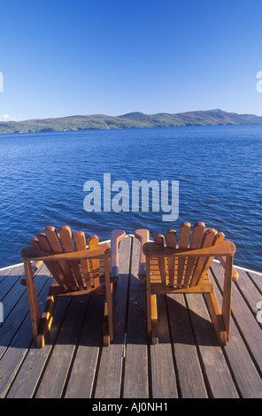 Two Adirondack chairs on a deck overlooking Lake George NY - Stock Photo