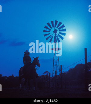 young woman riding horse by windmill in moonlight