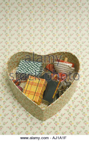 box in the form in an heart with little things in it - Stock Photo