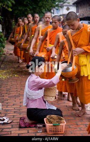 Local women give rice Alms to novice monks in Luang Prabang Laos - Stock Photo