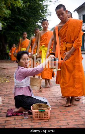 Local women give rice Alms to monks in Luang Prabang Laos - Stock Photo