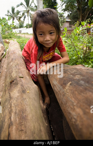 Small girl searches for fungi in a wood pile near Luang Prabang Laos - Stock Photo