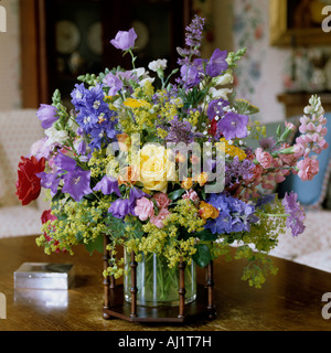 Assorted flower arrangement in glass vase with wooden frame.