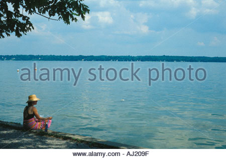 Woman in a straw hat relaxing by the water - Stock Photo