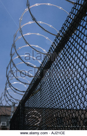 Detail of fence with razor wire on top - Stock Photo