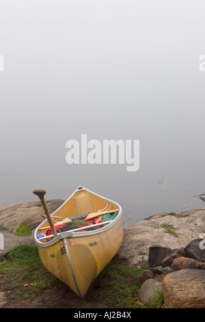 Canoe on shore of lake in Algonquin Provincial Park - Stock Photo