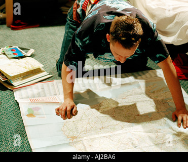 young male in bedroom leaning over map - Stock Photo