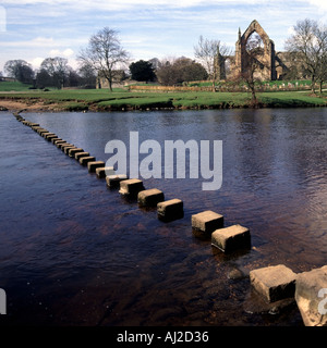 River Wharfe at  Bolton Abbey also known as Bolton Priory stepping stones to ruins of  Augustine Priory in Yorkshire - Stock Photo