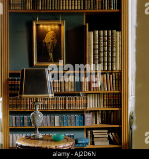 Decorative display of antique books and an oil painting in the library of a historic German stately home - Stock Photo