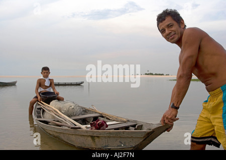 A father and son head off for a day fishing from their dug out canoe on the Rio Tapajos, a tributary of the Amazon - Stock Photo