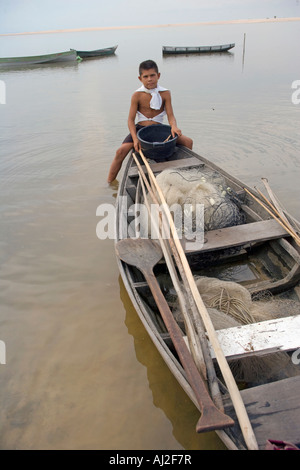 A son waits for his father to head off for a day fishing from their dug out canoe on the Rio Tarajos - Stock Photo