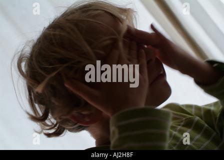France portrait of a little girl hiding her eyes - Stock Photo