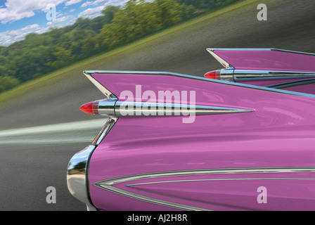 Pink Cadillac 1959 Fleetwood Car Detail of Rear Fins While Driving On Road With Motion Blur, Michigan USA - Stock Photo