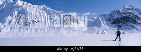 USA Alaska Denali National Park MR Mountain climber snowshoes along Kahiltna Glacier near climbers base camp on - Stock Photo