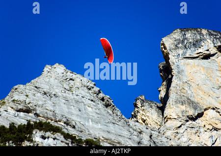 A paraglider sails through high mountains in the Interlaken Valley, Interlaken, Jungfrau Region, Switzerland - Stock Photo