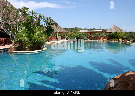 View of a Swimming pool and huts in a resort in Kerala, India. - Stock Photo