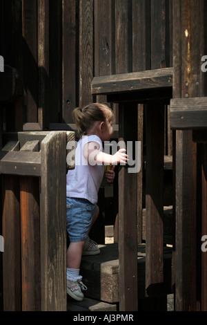 Toddler girl playing on wood playground. - Stock Photo