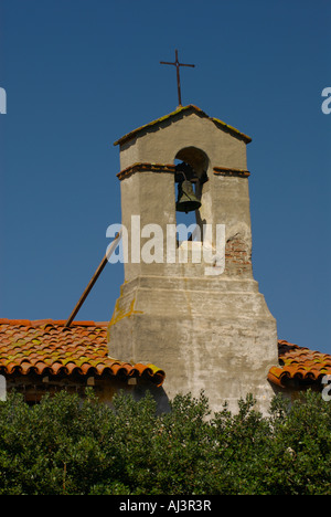 Wrought iron cross on the brick and adobe bell tower against a clear blue sky at the Mission at San Juan Capistrano, - Stock Photo