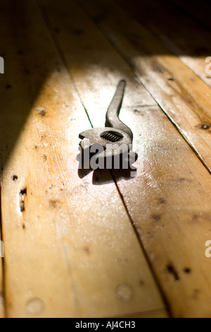 Sunlit wooden floorboards with wrench - Stock Photo
