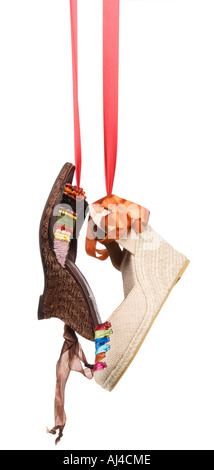 Ladies fashion shoes hanging on a ribbon - Stock Photo