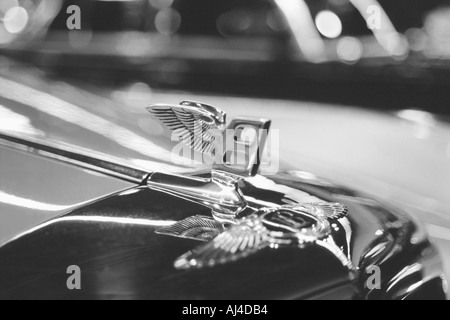 Shiny chrome flying B Bentley luxury classic car hood ornament - Stock Photo