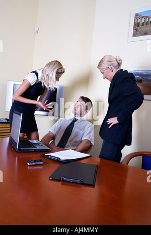 two girls mobbing their male colleague in the office - Stock Photo