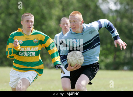action from schoolboy gaelic football player running with the ball being persued belfast county antrim northern - Stock Photo