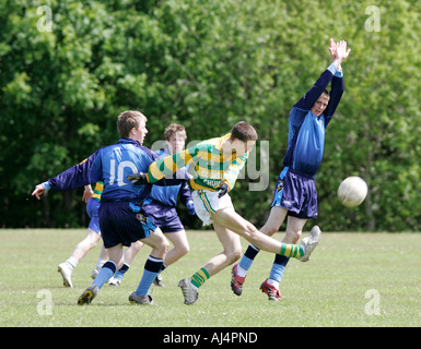 action from schoolboy gaelic football player kicking the ball surrounded by opposing players including one diving - Stock Photo