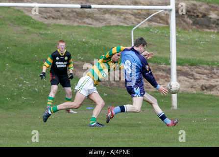 action from schoolboy gaelic football player kicking ball towards goal fending off opposing player - Stock Photo