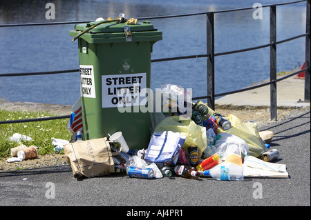 litter piled up next to a street litter only green wheelie bin by a fence on the pier Galway city - Stock Photo