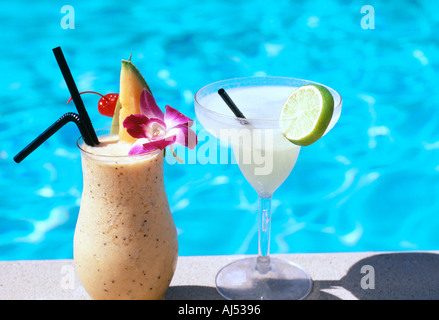 Exotic Cocktails by the swimming pool Sunshine summer holiday - Stock Photo