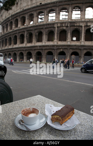Half full cup of cappuccino and a part eaten neapolitan chocolate pastry on a street cafe table next to the Colosseum - Stock Photo