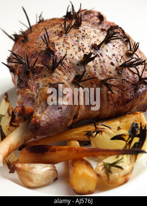 A whole roast leg of lamb with roasted parsnips onions and garlic - Stock Photo