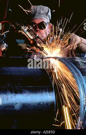 Male Caucasian pipe cutter with acetylene torch cutting oil pipeline sections - Stock Photo