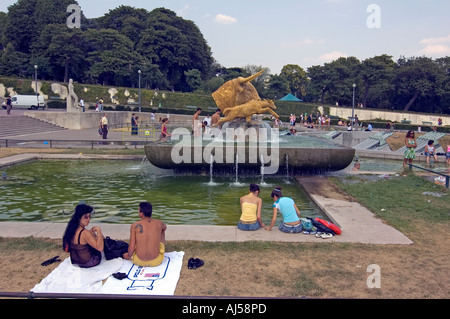 People relaxing near the fountain and pond of the Champ de Mars esplanade during the heatwave, Paris, France. - Stock Photo