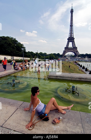 Woman relaxing near fountain and pond of the Champ de Mars esplanade during the heatwave, Paris, France. - Stock Photo