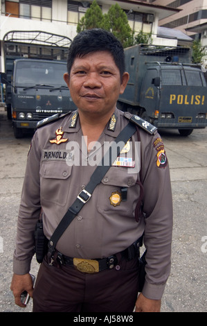 Portrait of an Indonesian police officer in Jayapura, with anti-riot trucks in the background, West Papua, Indonesia - Stock Photo