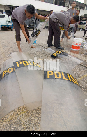 Indonesian police officers washing their anti-riot shields at their central compound in Jayapura, West Papua, Indonesia. - Stock Photo