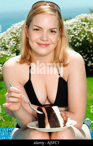 Young woman indulging in chocolate cake - Stock Photo