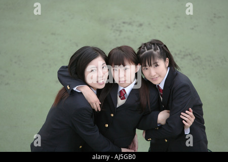 Three high school girls with arms around each other smiling - Stock Photo
