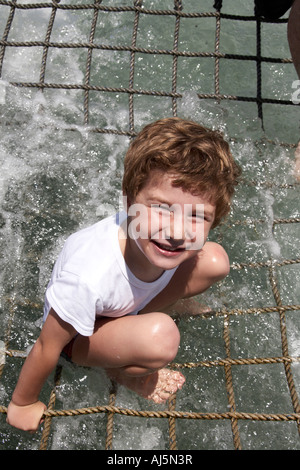 Young boy child smiling in splashing water of cruise ship boom net near Hawks Nest Port Stephens New South Wales - Stock Photo