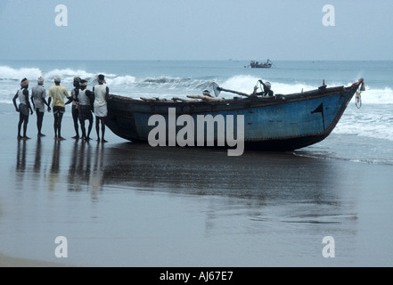 Fishermen preparing to launch their boat from the beach at dawn - Stock Photo