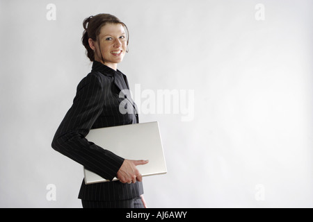 young woman in bussiness outfit with laptop under her arm, Germany - Stock Photo