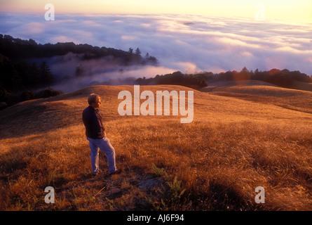 Man standing on hillside above fog near San Francisco California USA Model Released Image - Stock Photo