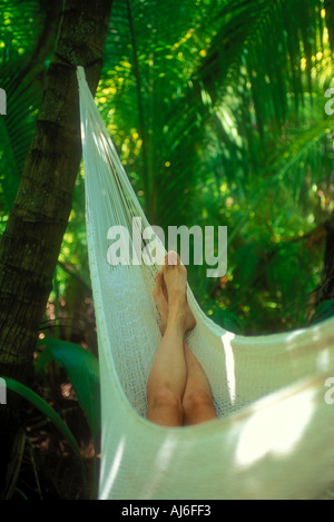 Womans legs in hammock surrounded by green tropical foliage in Belize Caribbean Model and Property Released Image - Stock Photo