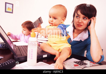 Woman sitting at the desk with her children while talking on the phone and using her laptop. - Stock Photo
