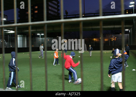 childrens urban football match being played under motorway flyover at night - Stock Photo