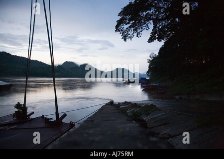 boats moored at the ferry pier for the night on the Mekong river at Luang Prabang in Loas - Stock Photo