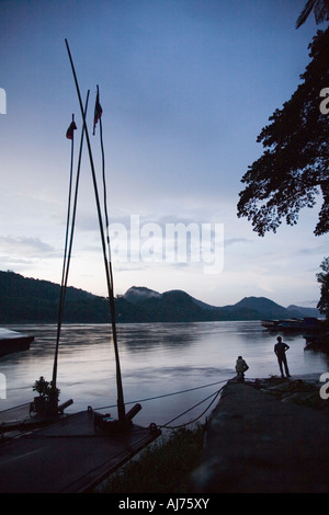 boats moored at the ferry pier for the night on the Mekong river at Luang Prabang in Laos - Stock Photo
